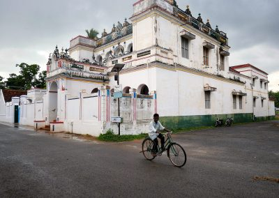 Boy on a bike in front of a Chettinad mansion
