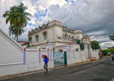 Man walking with an umbrella past a Chattinad mansion
