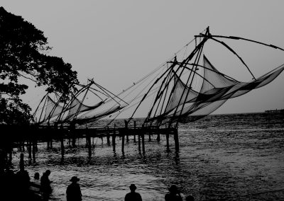 Chinese fishing nets with people watching b & w Fort Kochi